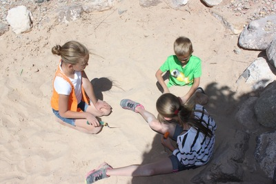 Kid learning about excavation in the sand